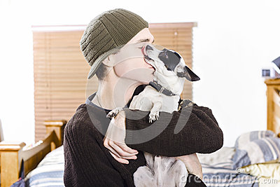 Small dog kissing his male owner. Pet love