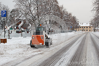 Small excavator bobcat working on the street