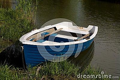 Small fishing rowboat floating
