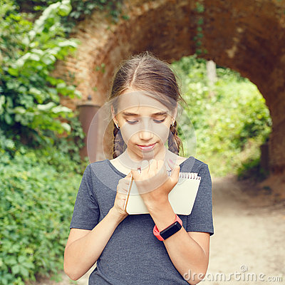 Free Small Girl Drawing In Notebook Near Arch Bridge Royalty Free Stock Photos - 74222988