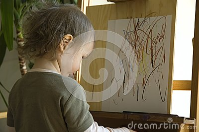 Small girl drawing at a wooden easel