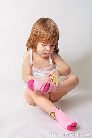 Free Small Girl Is Puting On The Socks Stock Photo - 4552480