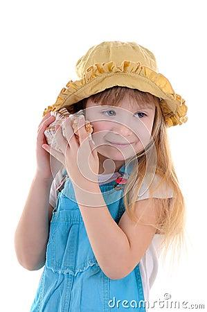 Small girl listens a sea shell