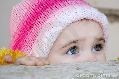 Small girl looks out behind a parapet