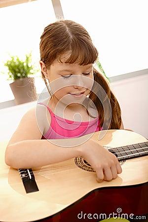 Small girl playing guitar