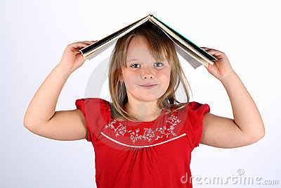Small girl in red holding a book on her head