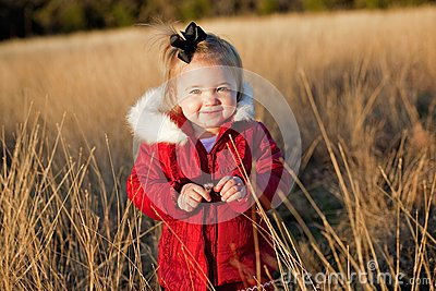Small girl in red jacket in a field