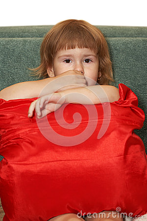The small girl with a red pillow