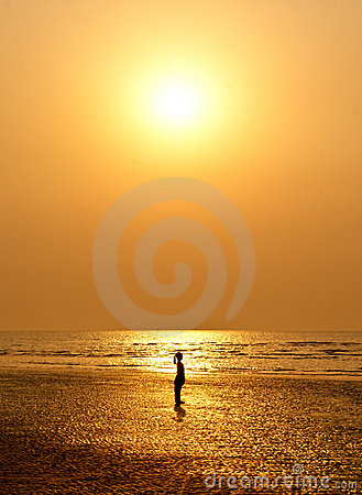A small girl silhouetted against sun set