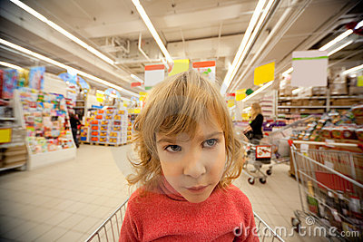 Small girl sit in shoppingcart in supermarket