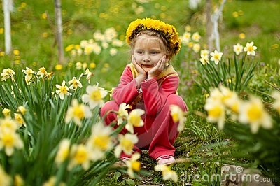 Small girl sitting in the spring garden