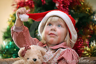 Small girl with toy near christmas tree