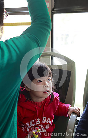 Small girl watching tv on the bus Editorial Stock Image