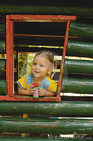 Small girl and wooden house