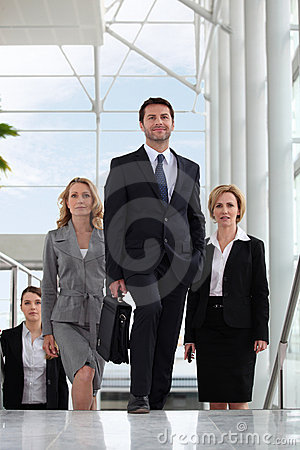 Small group of executives walking up stairs