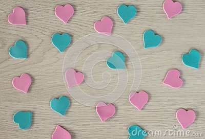 Small hearts of pink and blue color lie on a white wooden table Stock Photo