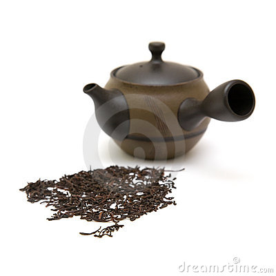 Small individual ceramic teapot and scattered tea