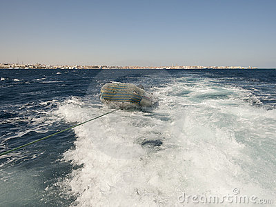 Small inflatable boat in ships wake