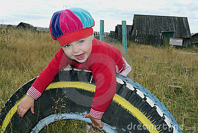 Small joyful girl on a wheel in village