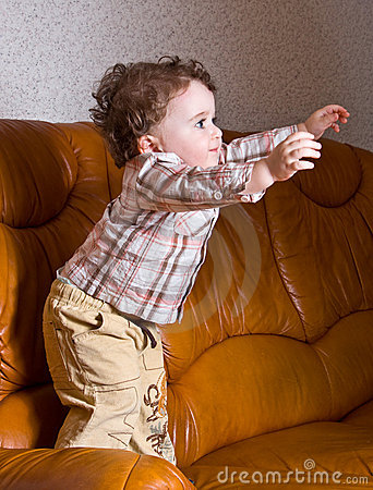 Small kid with curly hair on a leather brown sofa