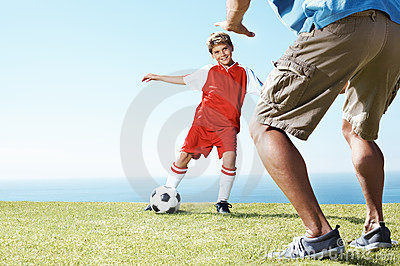 Small kid playing football with his father