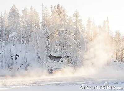 Small log cabin behind vaporing river