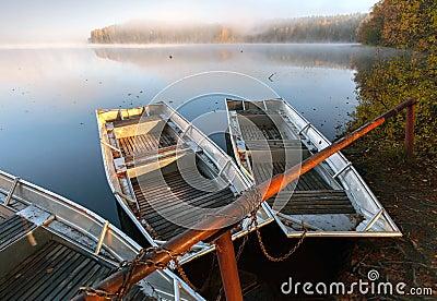 Small metal rowboats on still foggy lake coast
