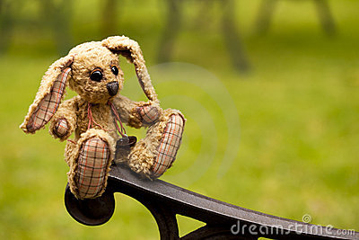 Small rabbit soft toy sitting in an iron bench