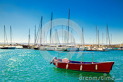Small red boat in front of the yachts
