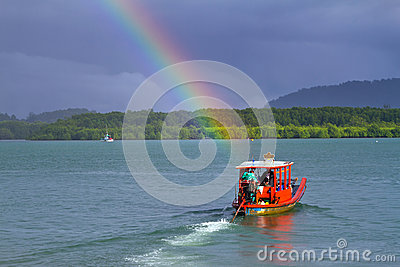 Small red boat on the river with rainbow