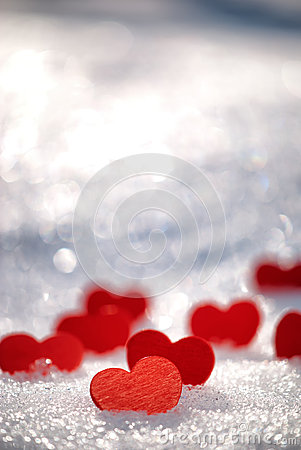 Small red hearts on snow