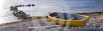 Small row boat laying on a pebble beach