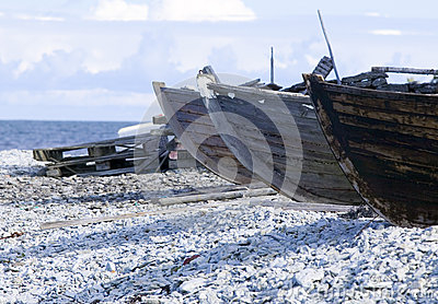 Small row boats laying on a pebble beach