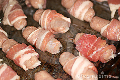 Small sausages wrapped with bacon ready to cook.