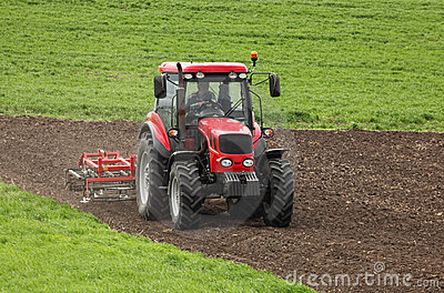 Small scale farming with tractor and plow in field