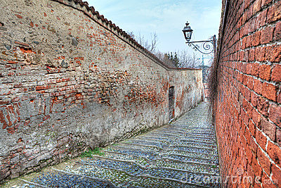 Small street among old walls in Saluzzo, Italy.