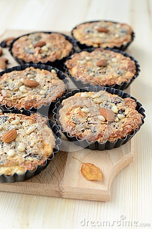 Small tarts with nut filling on a wooden board.