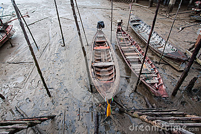 A small wooden fishing boat is run aground on the