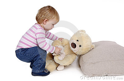 Small young girl lies down Teddybear