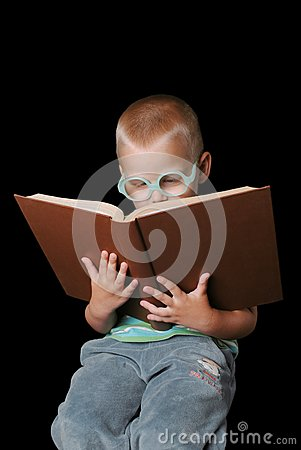 Smart boy with glasses reading book