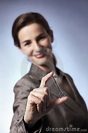 Smart business woman holding key between fingers