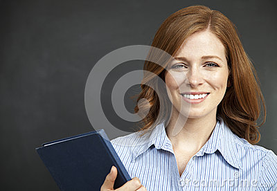 Smart female with red hair holding blue book