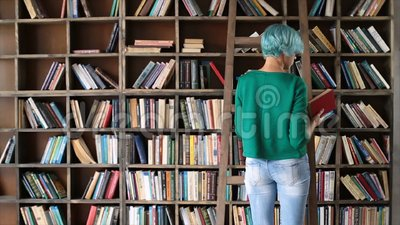 Smart girl selecting literature book in store stock video