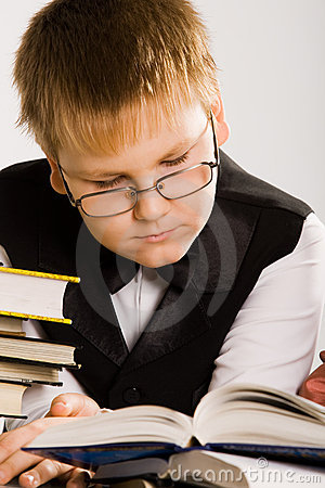 Smart looking school boy reading a book