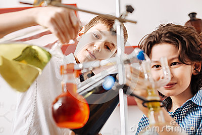 Smart serious boys using chemistry equipment