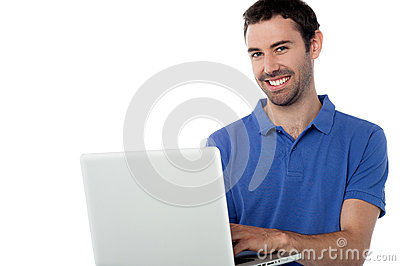 Smart smiling guy working on laptop