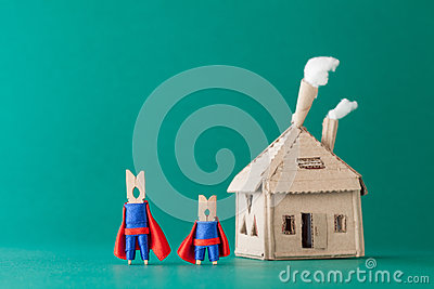 Smart and strong clothespin superheroes cardboard house. Big small super team characters on green background. soft Stock Photo