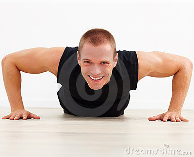 Smart strong man smiling while doing a pushup