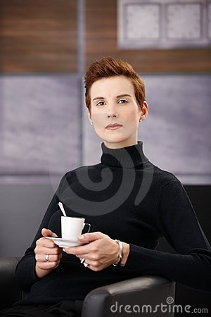 Smart woman having coffee in armchair