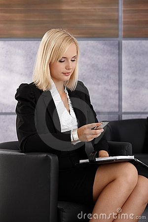 Smart young businesswoman checking phone